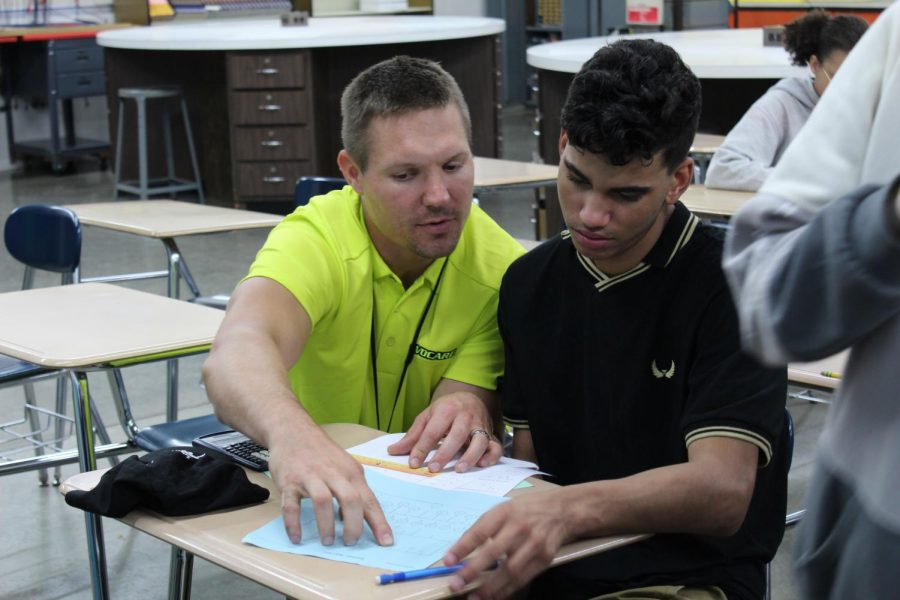 Technology education teacher Joshua Kasuboski helps a student in Applied Math.