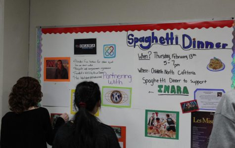 Communities students work on a display board in preparation for the Spaghetti Dinner to raise funds for children of war.